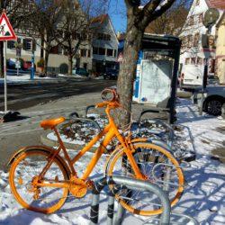 Ein oranges Fahrrad am Marktplatz